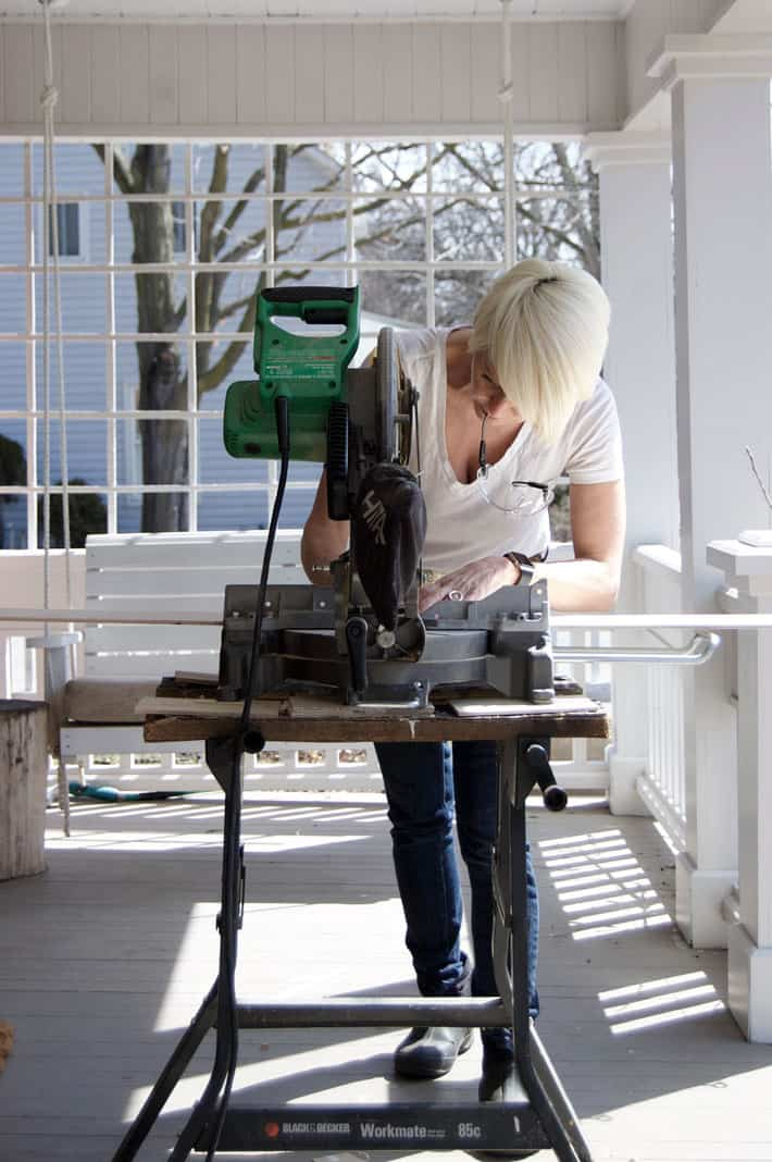 Woman cutting wood to length on outdoor porch.