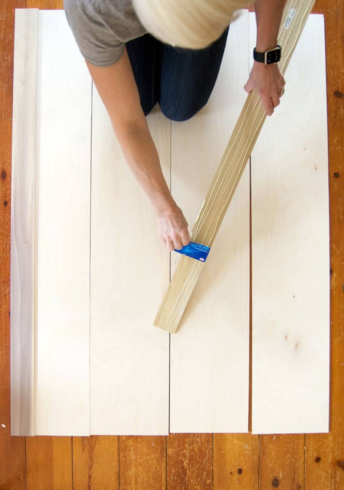 Spreading glue on wood trim with old credit card.