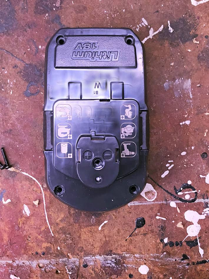 Overhead view of a rechargeable drill battery on paint splattered work bench.