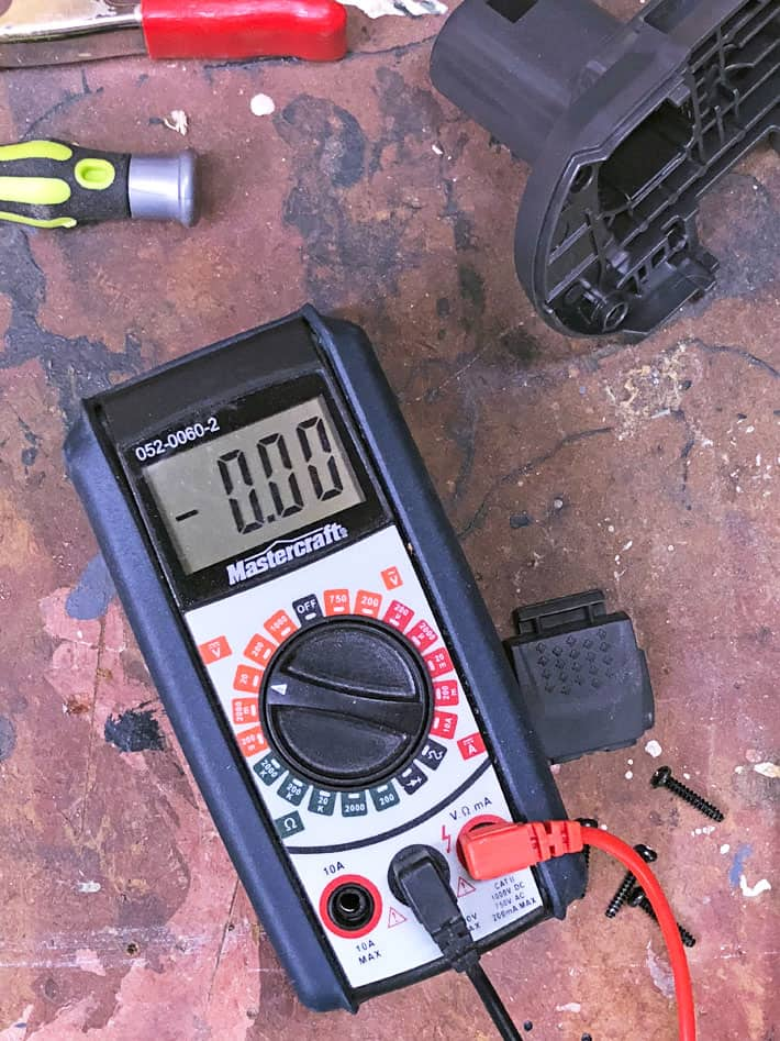 Multimeter on workbench with tools around.