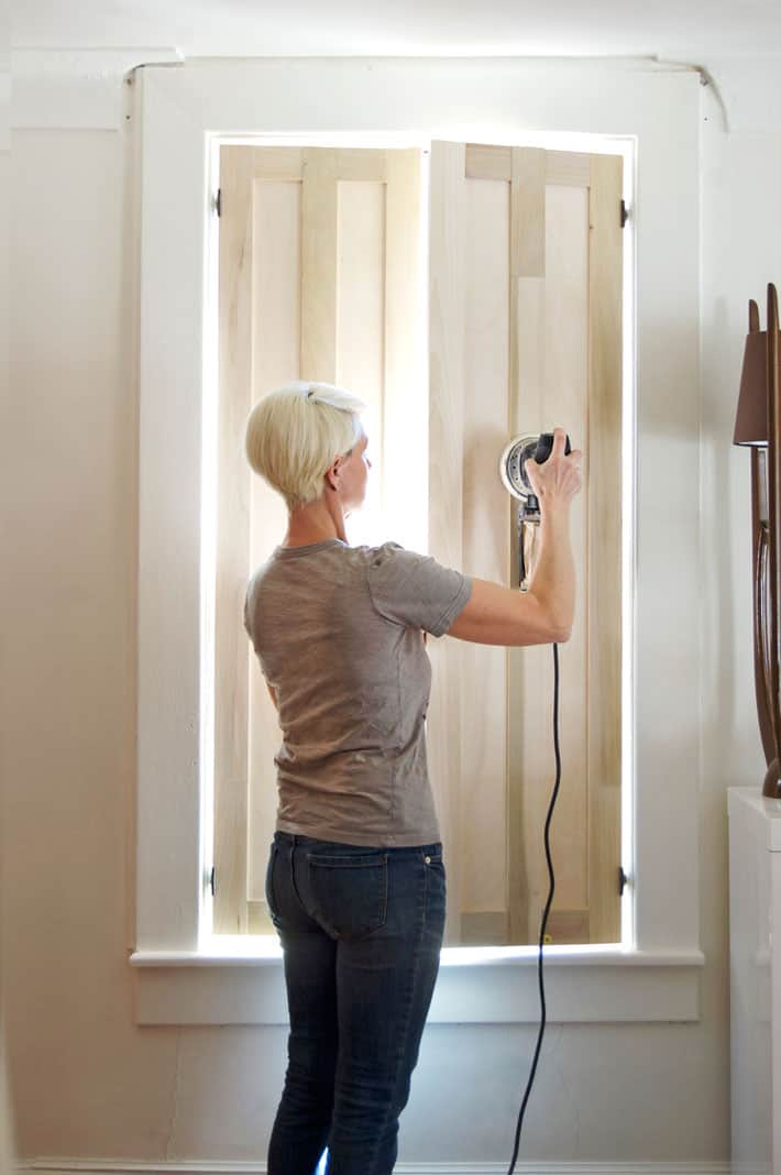 Sanding interior wood shutters with palm sander.
