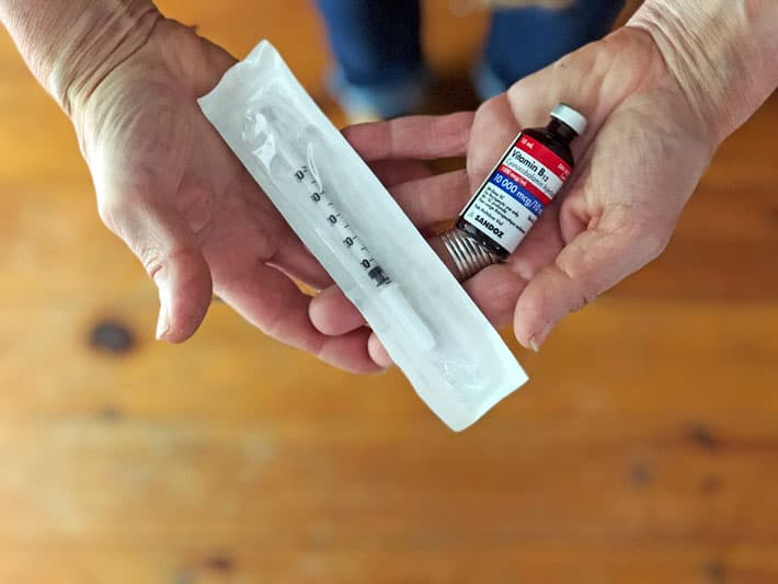 Hands holding a vial of vitamin B12 and syringe.