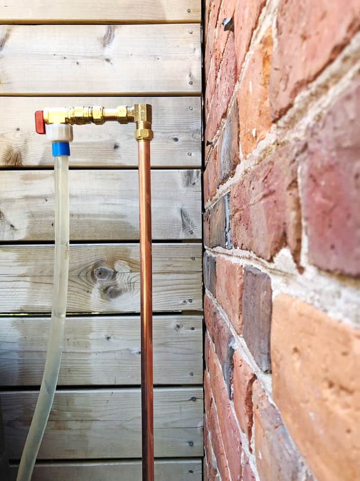 Newly replaced copper water pipe, outside against brick wall.