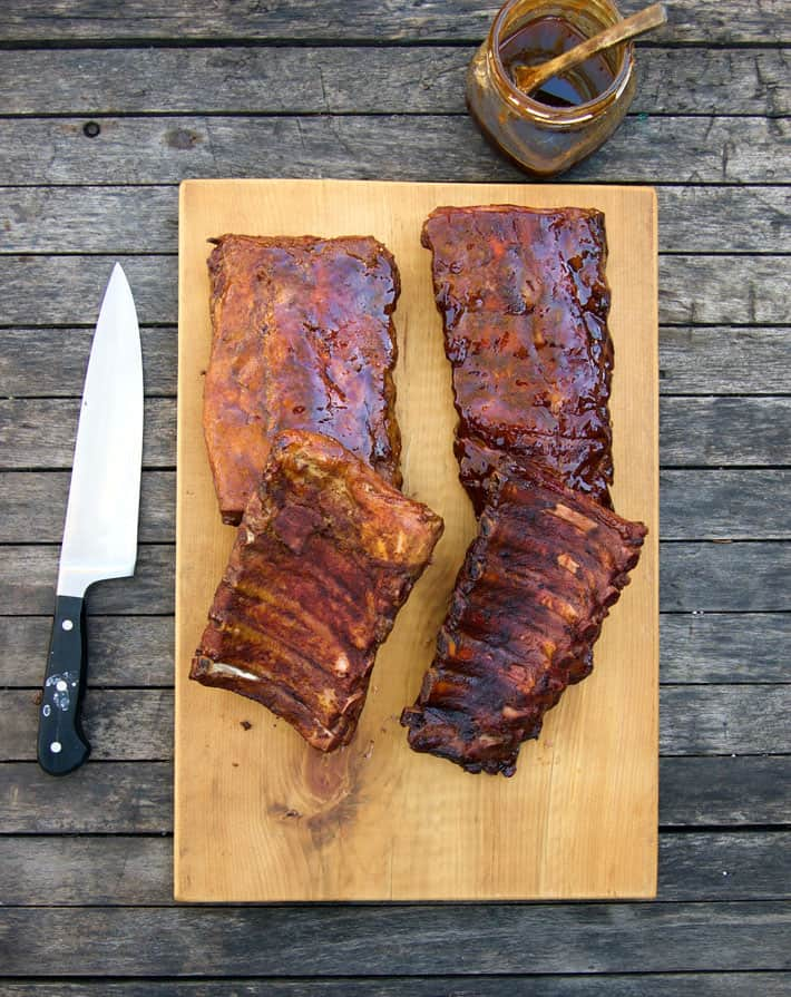 Beautiful racks of ribs on wood chopping block with knife and sauce to the side.