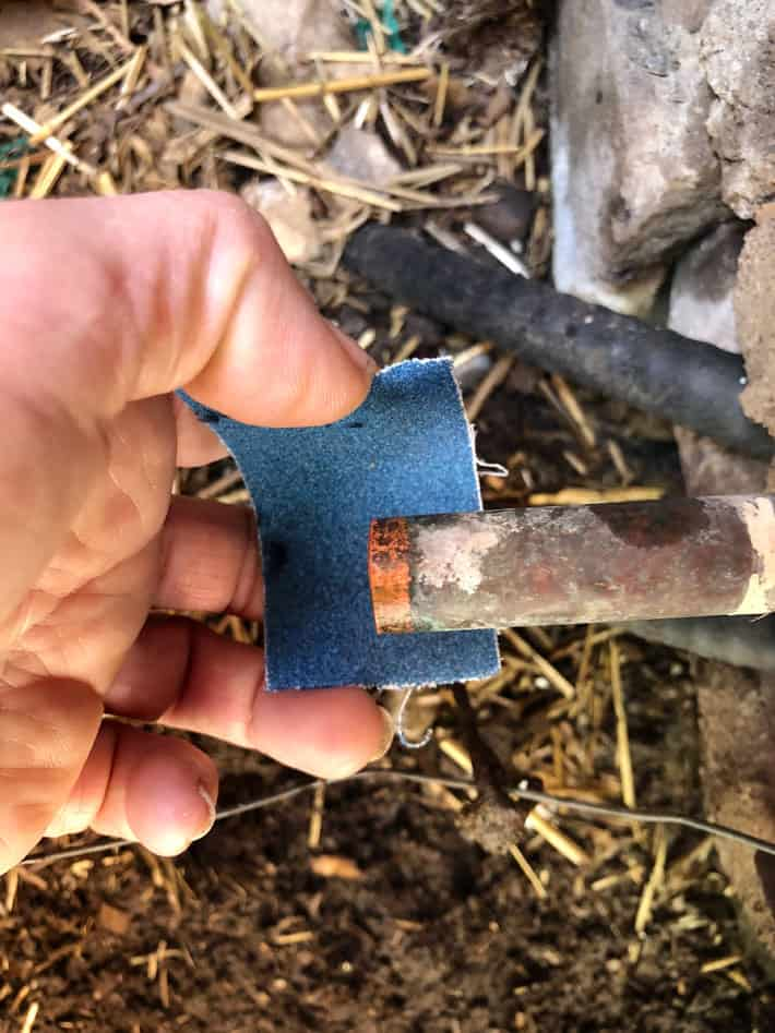 Sanding old copper pipe with blue sandpaper.
