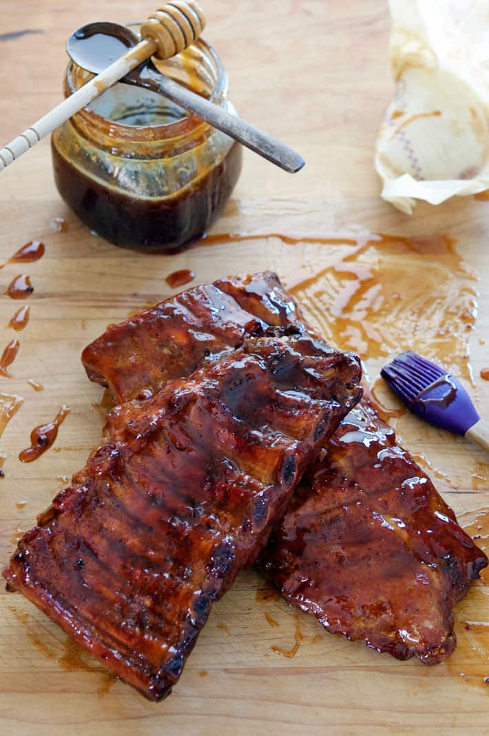 Rack of ribs, cut in half, slathered with sticky Maple Bourbon BBQ sauce on butcher block countertop.