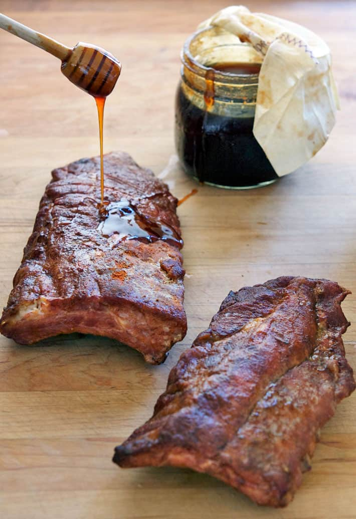 Gooey sauce being drizzed with honey dripper onto ribs.