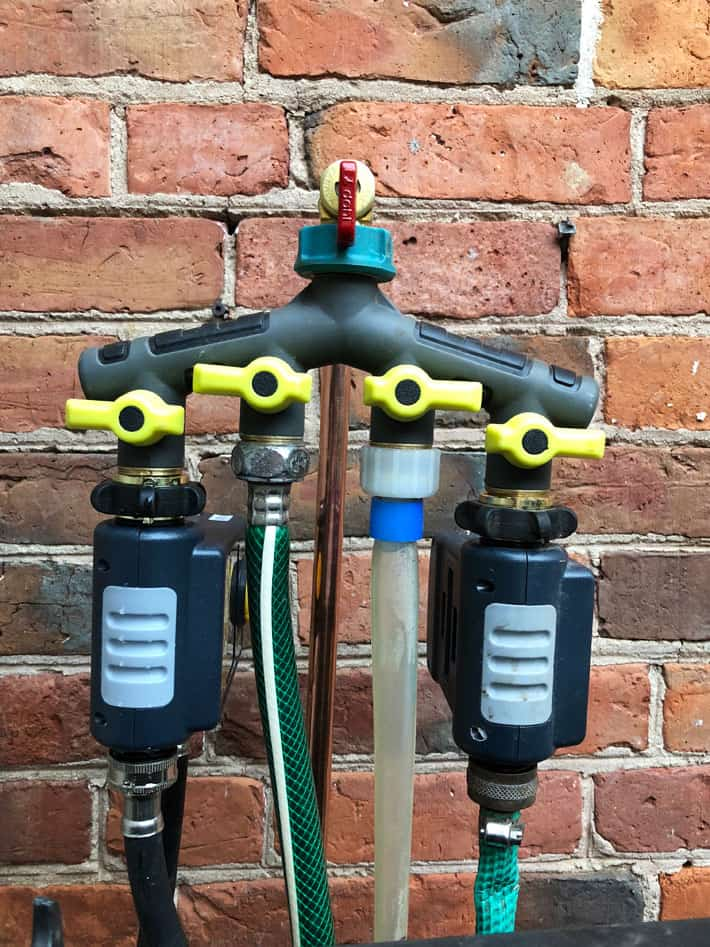 Four diverter tap with timers and hoses attached.