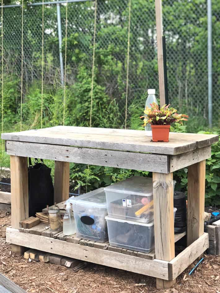 Potting table in garden with plastic storage containers underneath.
