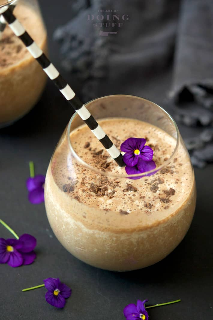 Chocolate banana smoothie in a frosty stemless wine glass sitting on a black background with deep purple violets scattered about.