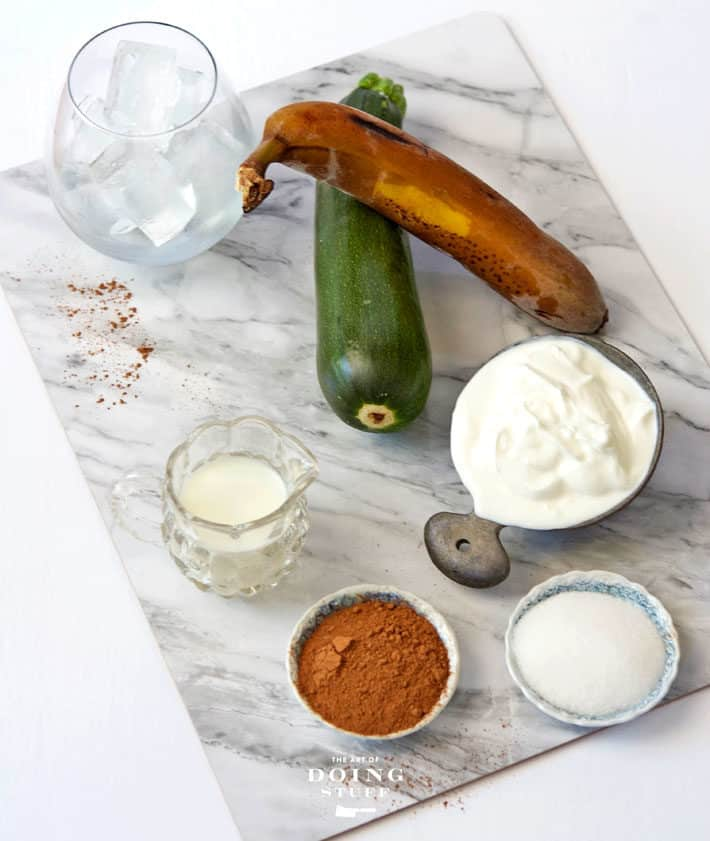 Overhead view of chocolate banana smoothie ingredients on a marble cutting board including a glass of ice, frozen banana, zucchini, milk, cocoa, sugar and yogurt.
