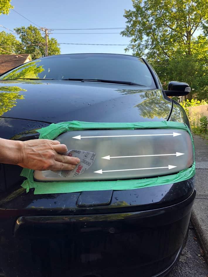 Sanding car headlight horizontally with wet 3000 grit sandpaper.