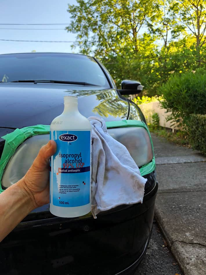 A bottle of isopropyl alcohol held up in front of a black car and headlight.
