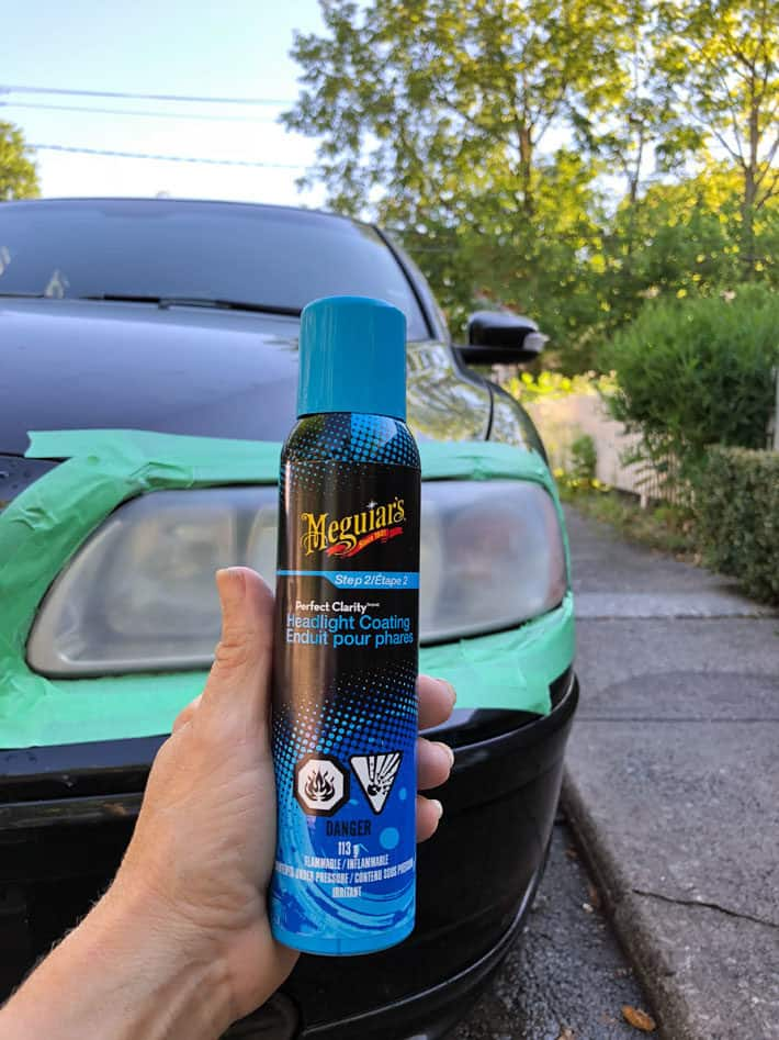 Meguiar's headlight coating can held up in front of cloudy headlight.