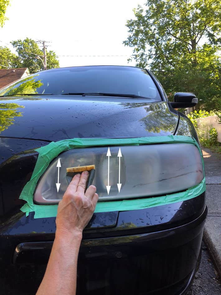 Sanding car headlight in a vertical motion using wet 1,500 grit sandpaper.