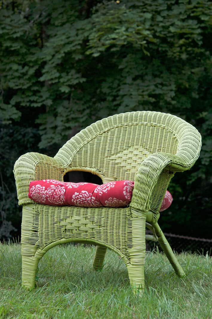 Green painted wicker chair on lawn with red cushion.