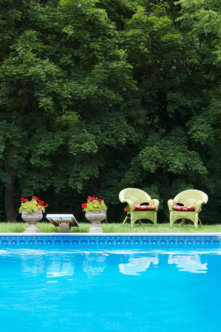 Green wicker chairs sitting on lawn beyond blue pool.