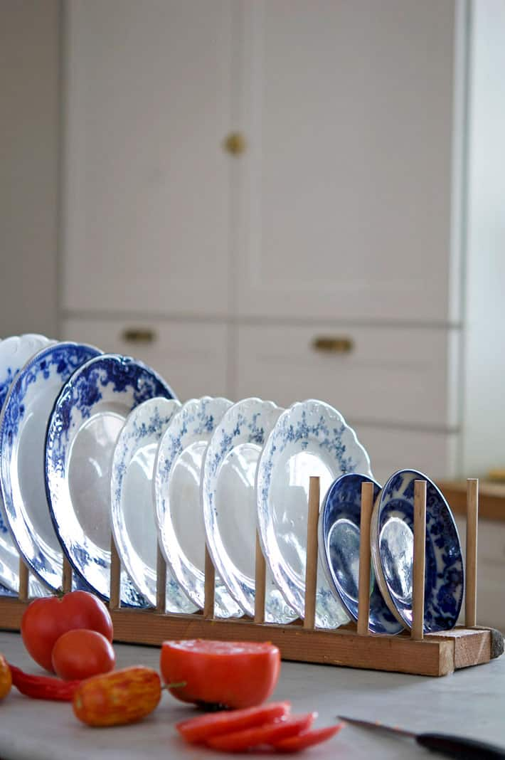 DIY plate rack on counter filled with flow blue plates.