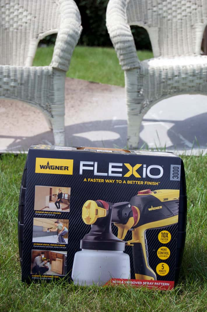Wagner Flexio 3000 in box sitting on lawn with white wicker chairs in background.