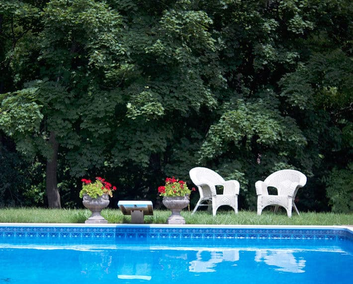 Two white wicker chairs sitting on grass beyond pool.