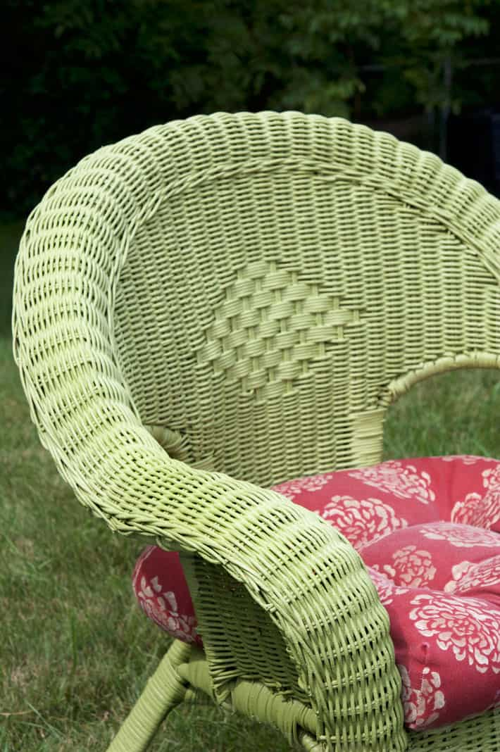 Green wicker chair sitting on lush lawn.