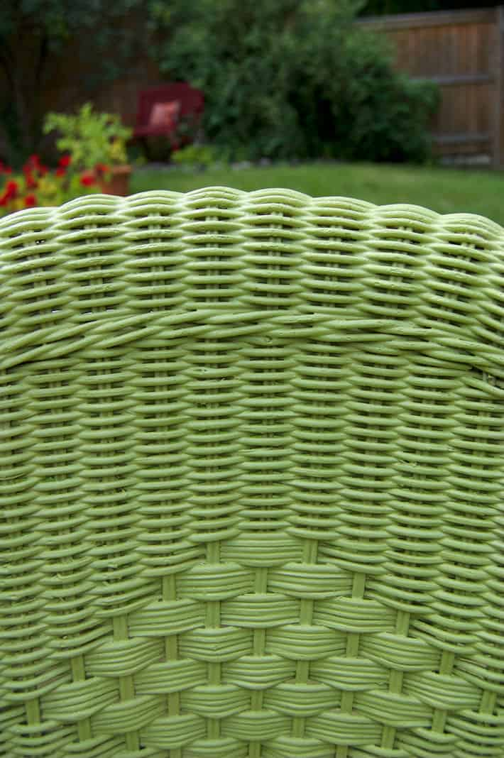 Close up shot of intricate wicker weaving, painted green.