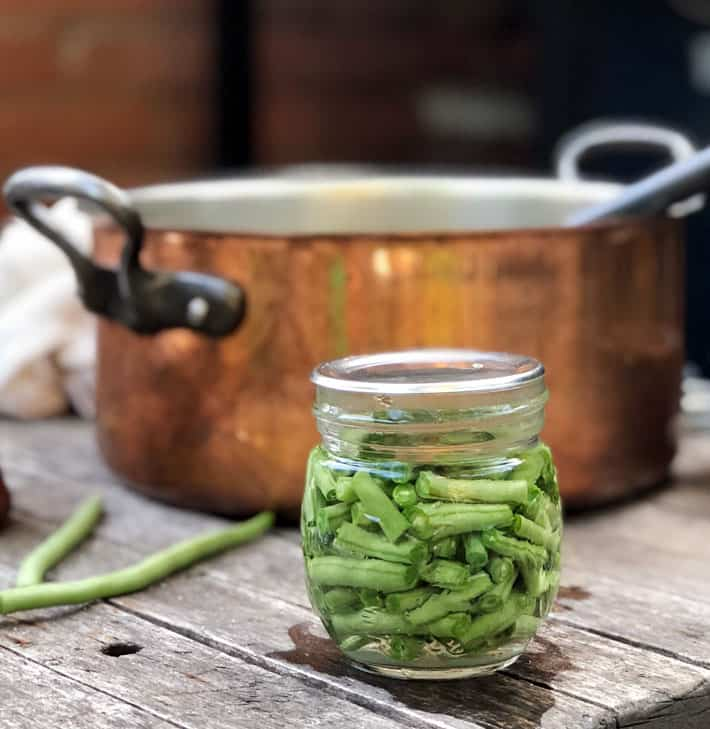 Small mason jar filled with fresh cut green beans in front of copper pot.