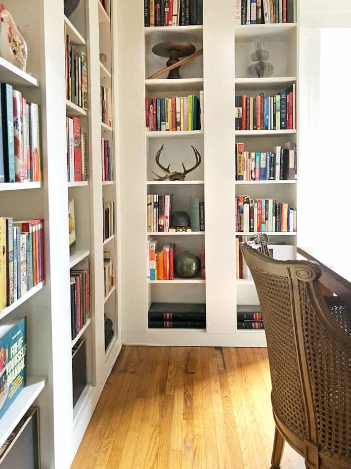 White Billy bookcases filled with eclectic pieces and books. Oak, thin strip flooring.