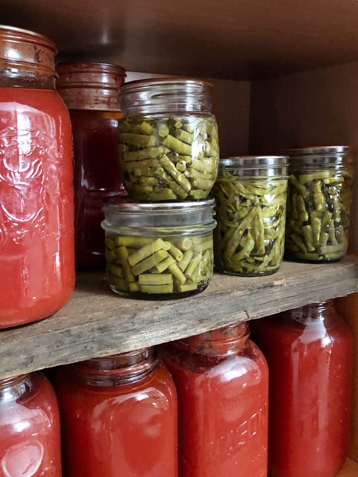 Pantry shelf of green beans and tomato sauce.