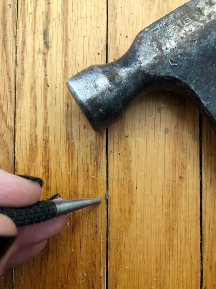 Countersinking nail in hardwood.