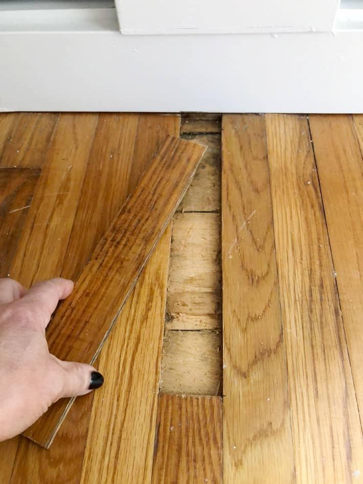 One strip of oak flooring removed to reveal heritage pine underneath.