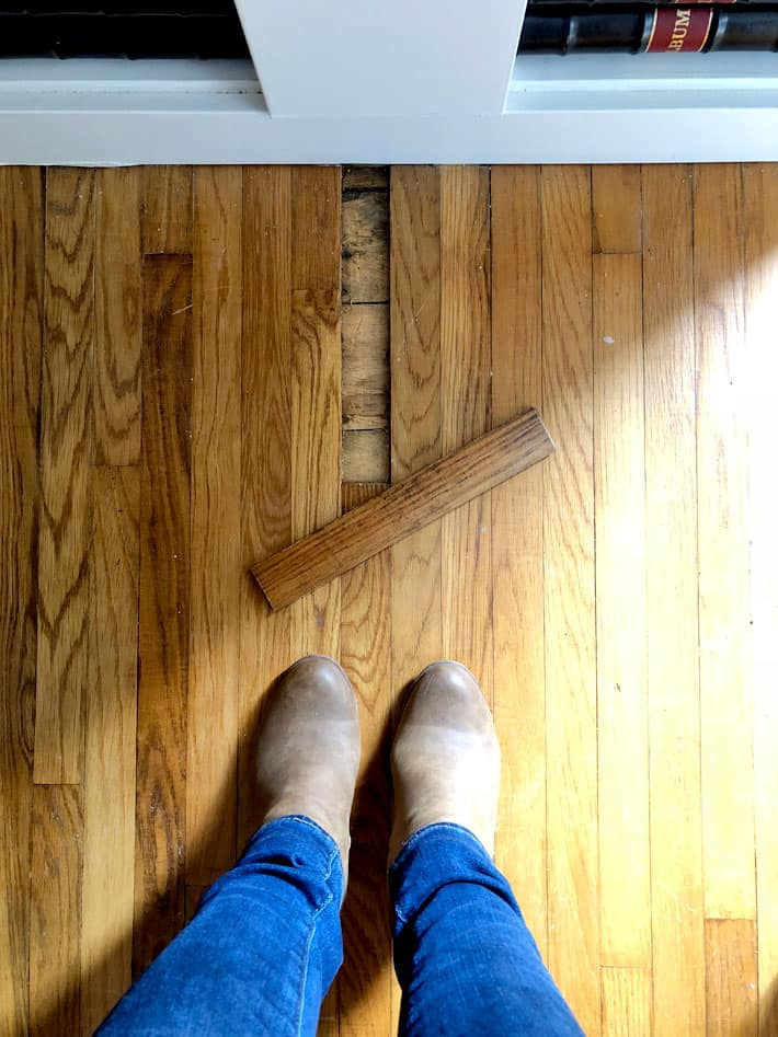 Single piece of oak strip flooring removed to reveal pine flooring.
