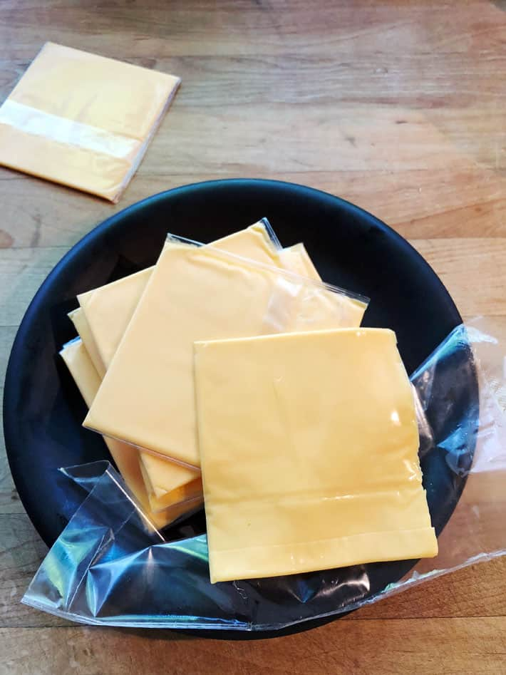 Stack of the classic plastic wrapped cheese on a black plate.