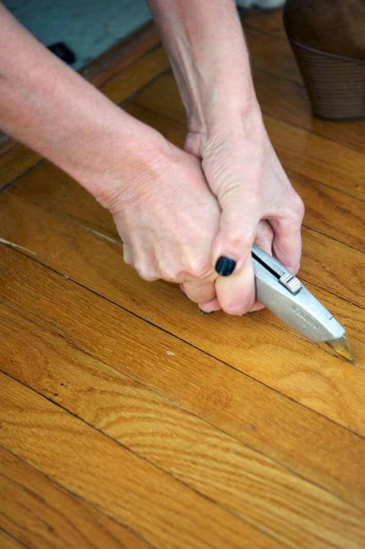 Cutting through oak tongue and groove strip flooring crack to remove single piece.