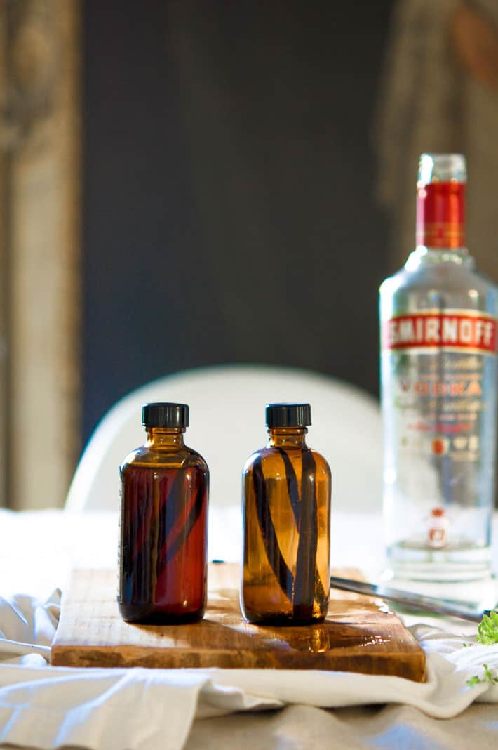 Amber bottles of homemade vanilla extract set on a cutting board with a bottle of vodka in the background.