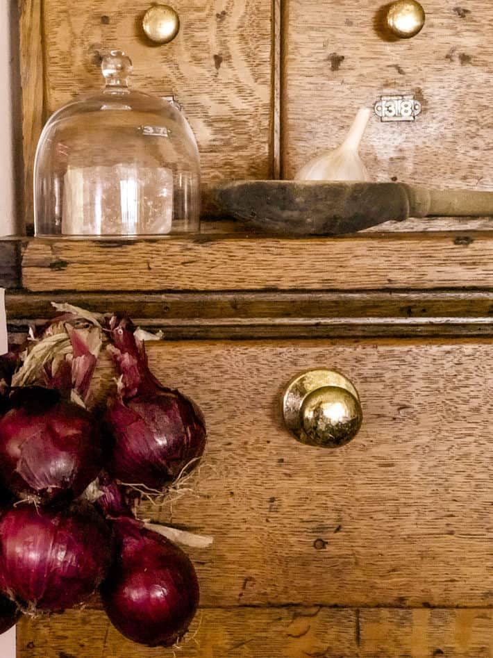Red onions hanging off the drawer of an antique wood cabinet.
