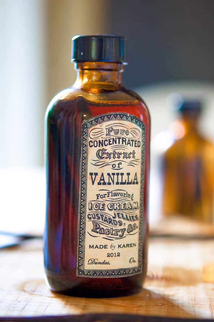 A glass amber bottle filled with homemade vanilla extract with an old fashioned looked label on it.
