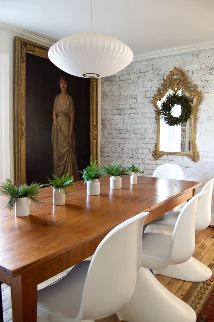 Antique brick wall painted white in dining room with harvest table and white Panton S chairs.
