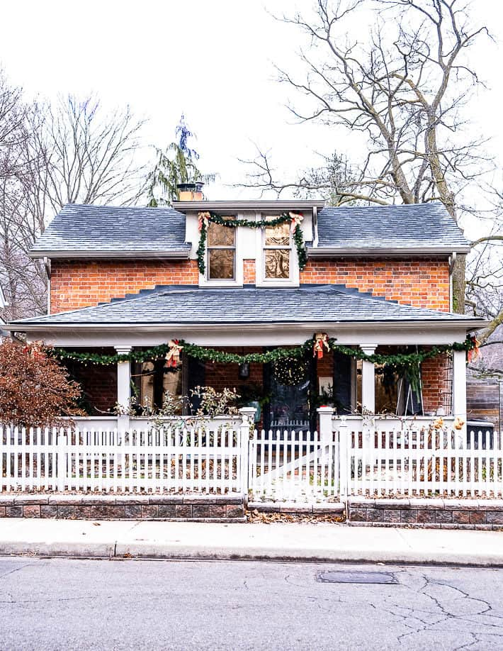 Ontario worker's cottage swagged with garland for Christmas, surrounded by a white picket fence