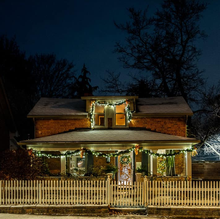 Beautiful historic red brick cottage surrounded by picket fence decorated for Christmas at night.