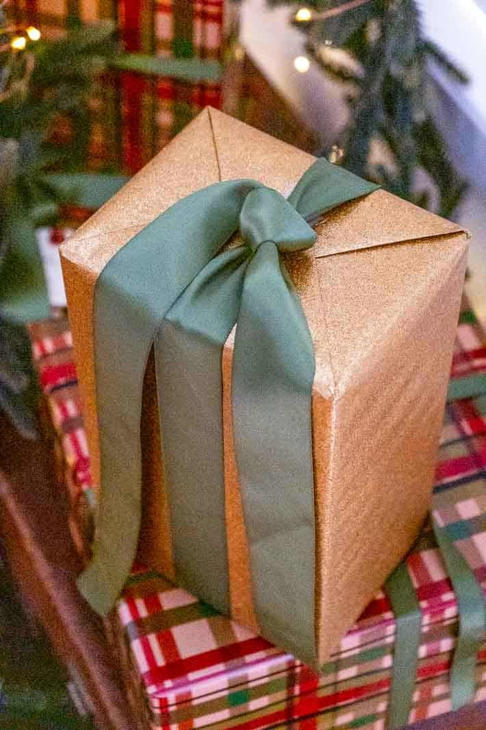 Christmas present wrapped in sparkly gold paper and a green satin ribbon.