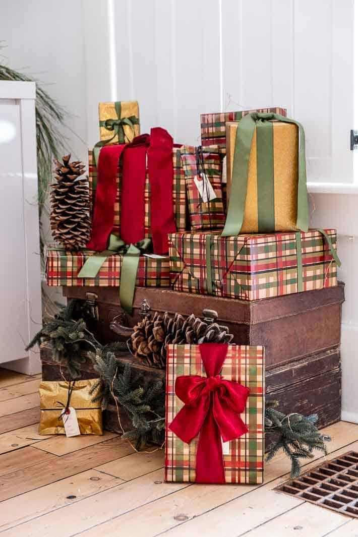 Presents wrapped for Christmas stacked on antique leather and wood suitcases.