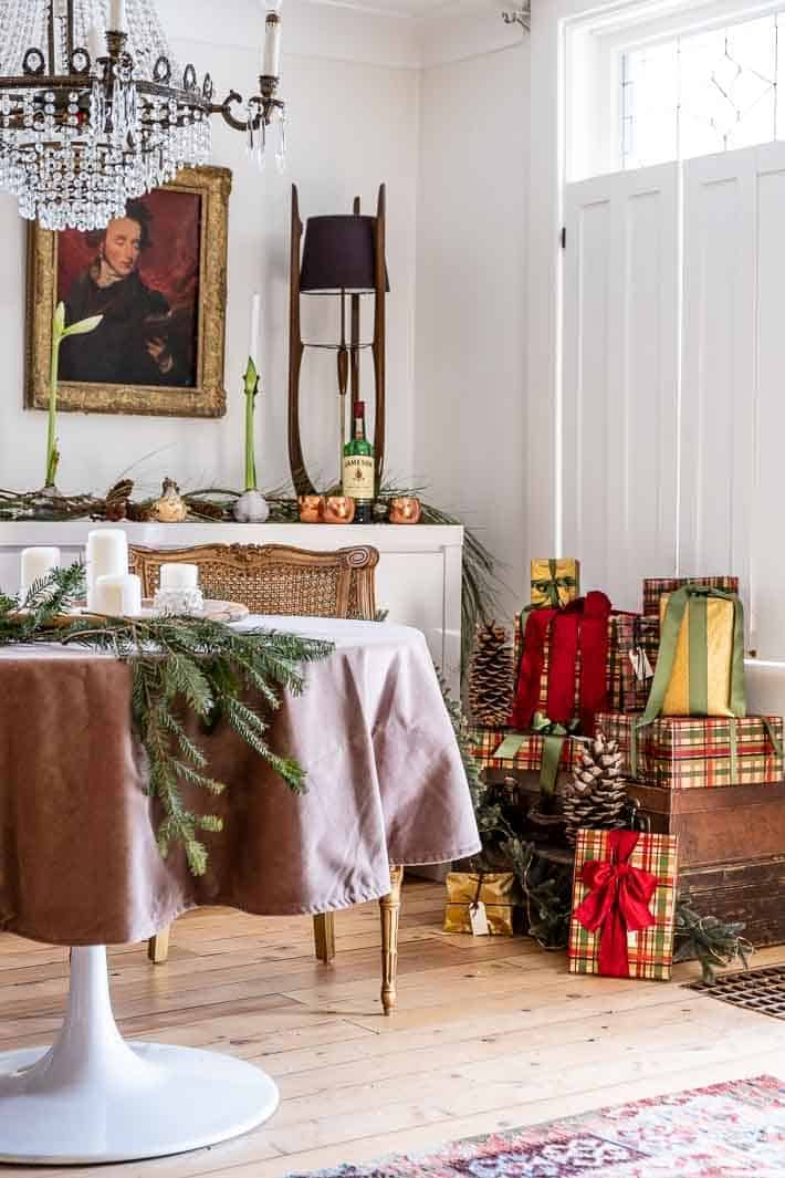 Classicly wrapped Christmas presents in an eclectic room decorated for the holidays.
