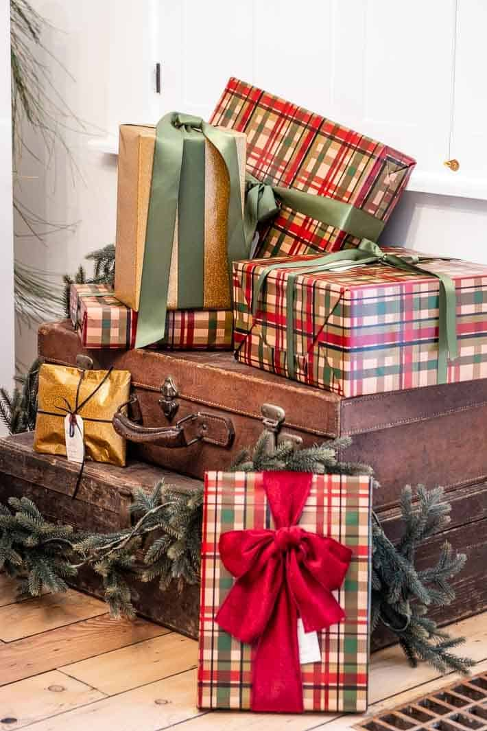 Christmas presents wrapped in gold paper and green and red plaid paper with velvet and satin ribbons.