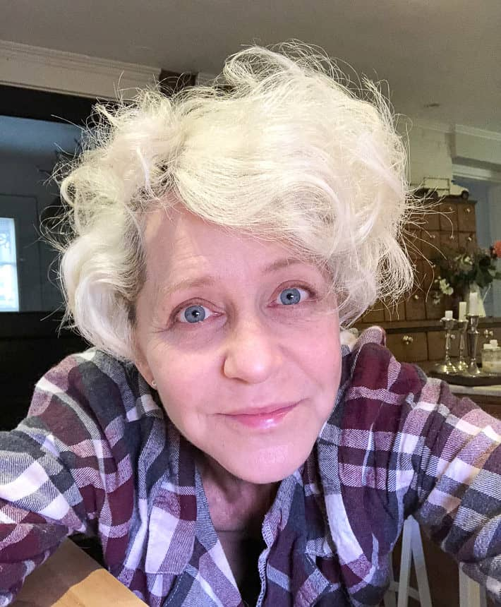 A photo of Karen, who is wearing a purple and gray checked shirt, after curling her short, blonde hair to emulate Charlize Theron.