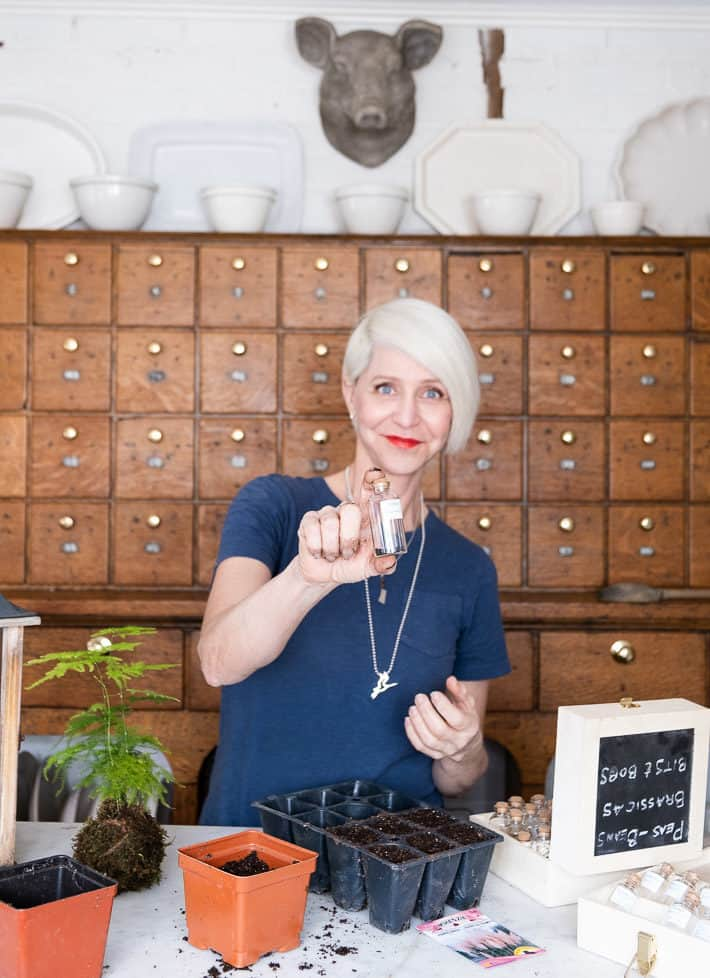 Karen Bertelsen holding up a small glass vial of onion seeds in front of an antique wood apothecary cabinet.