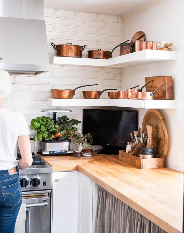 Maple butcher block counters glow with 2 floating shelves of gleaming copper pots hanging above.