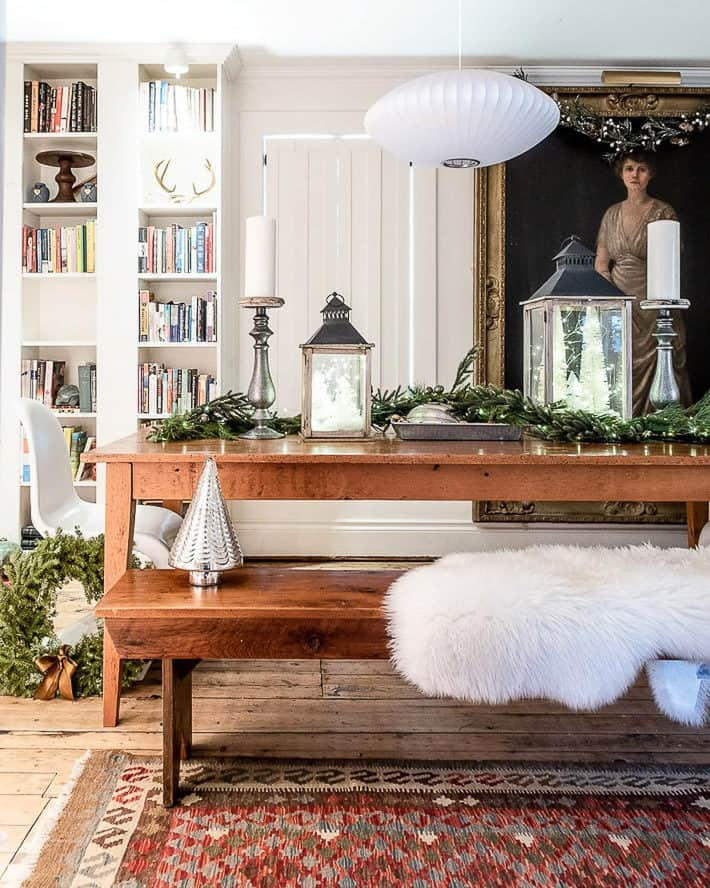 Cozy dining room decorated for Christmas with a pine harvest table filled with garland, candles and lanterns. A sheepskin throw lays on top of a pine bench.