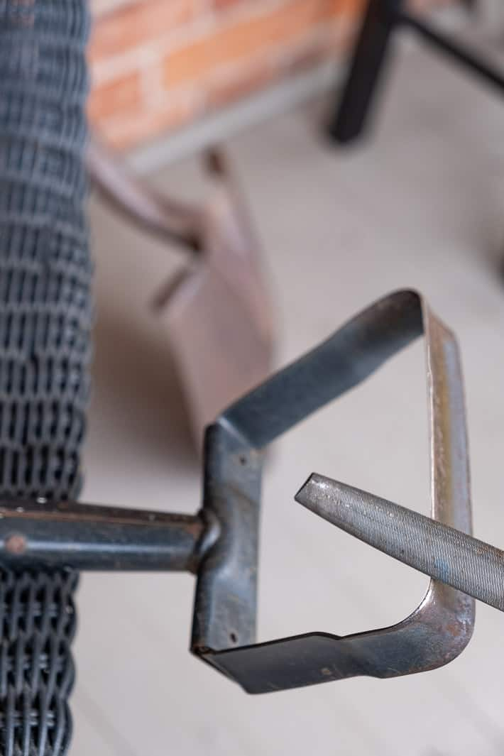 Sharpening a stirrup hoe with a metal bastard file while it rests on a black wicker chair on a front porch.