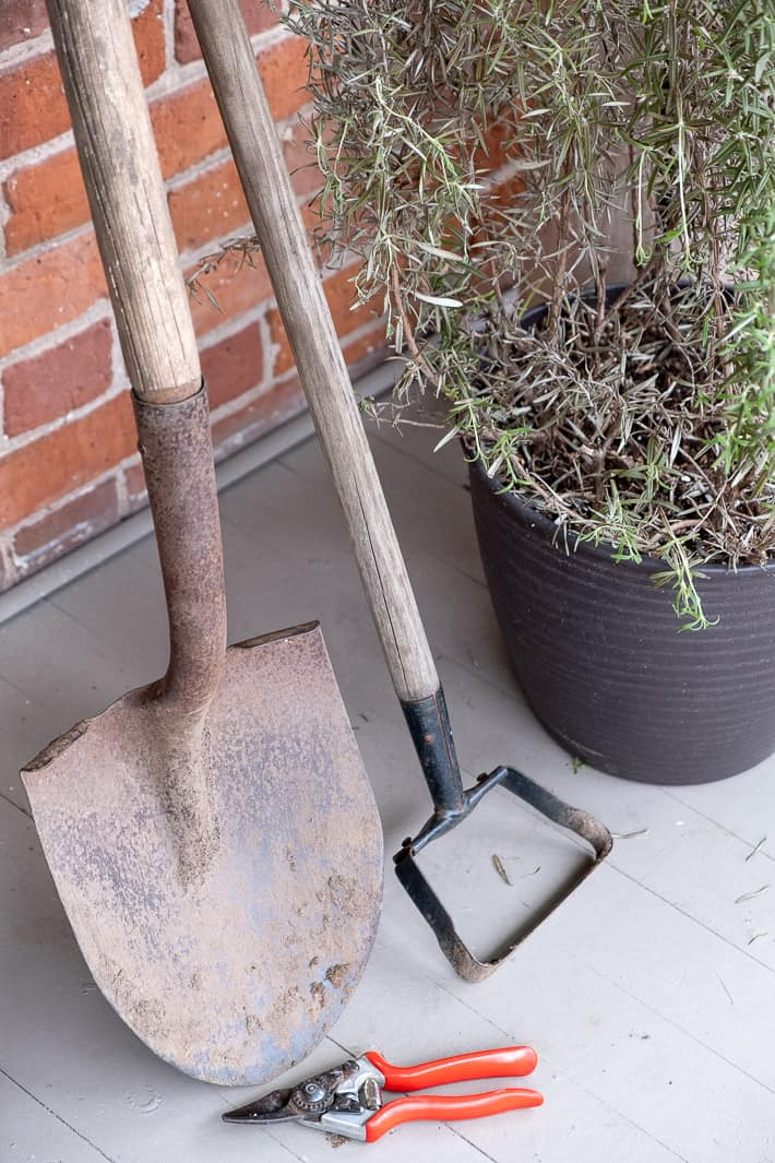 Trio of garden tools leaning against a brick wall before receiving routine maintenance like cleaning, sharpening and oiling.
